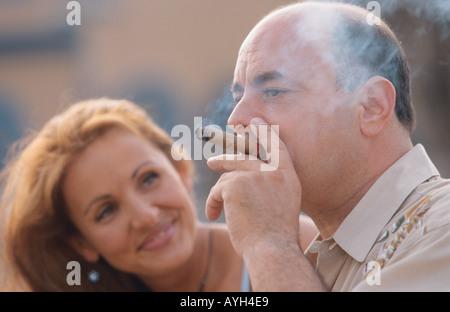 Woman admiring her man smoking a cigar - Stock Photo