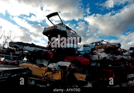 Scrapheap of worn out and abandoned cars piled high in a scrapyard in the British countryside - Stock Photo