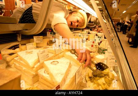 A deli assistant in uniform and hat stretches to reach cheese on her deli counter at   Waitrose supermarket - Stock Photo