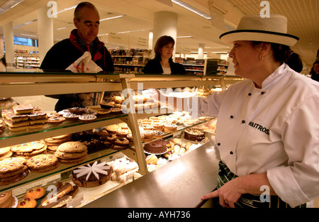 A shop assistant in uniform and hat on the patisserie counter at Waitrose, Britain's leading quality supermarket - Stock Photo