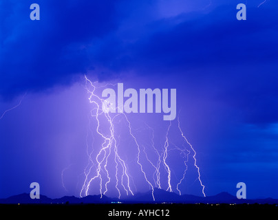 Lightning bolts strike a mountain range from a brilliant blue sky during a summer monsoon storm in Southern Arizona, - Stock Photo