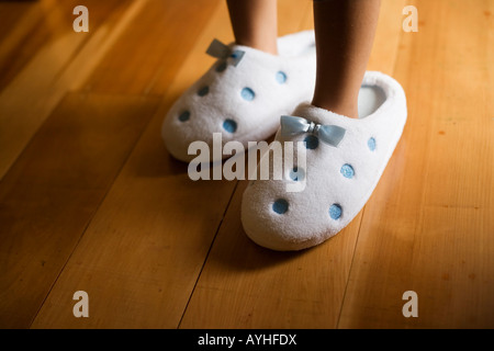 Girl aged four wears her mother s slippers - Stock Photo