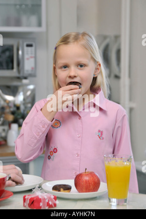 young 7-years old blonde girl eating a donut - Stock Photo