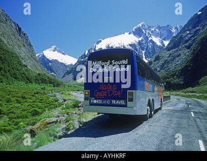 Milford Sound tour bus at Monkey Creek with Mount Talbot in Southern Alps on South Island  New Zealand - Stock Photo