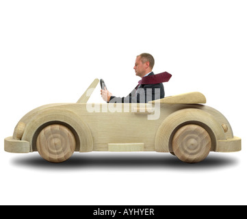 Concept image of a businessman driving to work in his environmentally friendly wooden car - Stock Photo