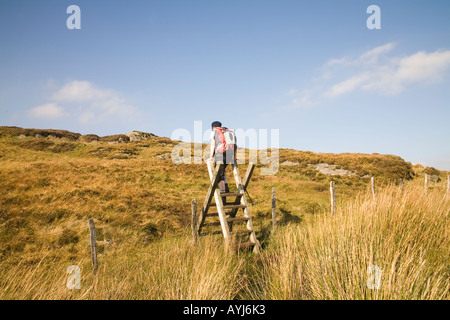 CAPEL CURIG CONWY NORTH WALES UK September Female walker climbing a stile high above Capel Curig on Cefn y Capel - Stock Photo