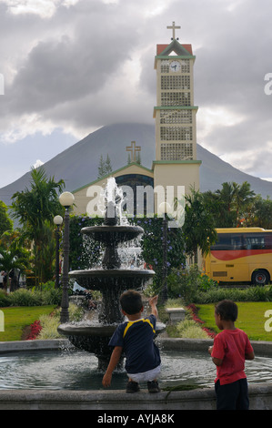 Two boys playing in the La Fortuna park fountain with church and Arenal Volcano Costa Rica - Stock Photo