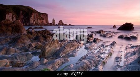 Rocky coast at sunset Bantham Devon England - Stock Photo
