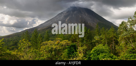 Panorama of active smoking Arenal volcano with storm clouds and  burning cinder blocks tumbling down slope Costa Rica
