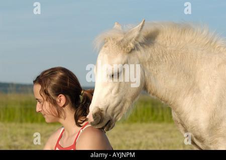Girl and Connemara pony foal - portrait - Stock Photo