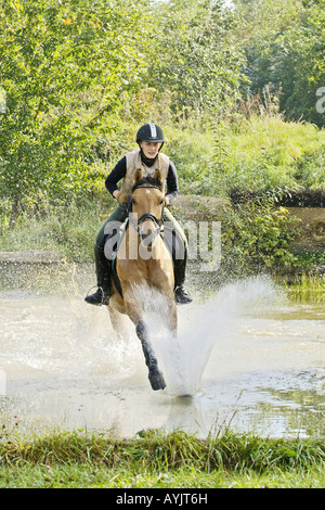 Young lady rider galloping through water - Stock Photo