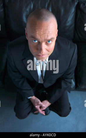 balding man in his 40s wearing a black suit and string tie seen from above is sitting on a black leather couch looking - Stock Photo