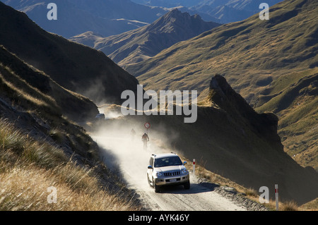 Four Wheel Drive and Mountain Bikers on Infamous Road into Skippers Canyon near Queenstown South Island New Zealand - Stock Photo