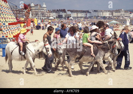Adults & children on & around donkeys for donkey ride for kids along Weymouth sandy family summer beach holiday - Stock Photo
