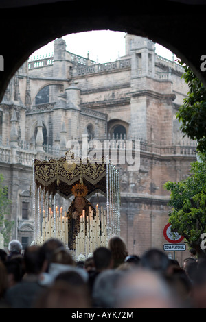 Framed view of a Holy Week float with the Virgin image in front of Seville's Cathedral, Spain - Stock Photo