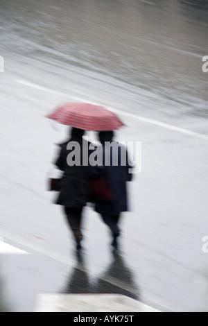 people crossing road with umbrella in rain - Stock Photo