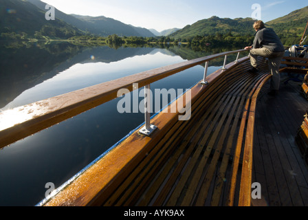 Ullswater steamer cruising on the lake near Glenridding in early morning summer sun with a passenger looking at the view