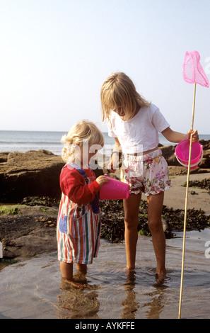 Uk cornwall two 9 12 year old girls sitting cross legged for Kids fishing nets