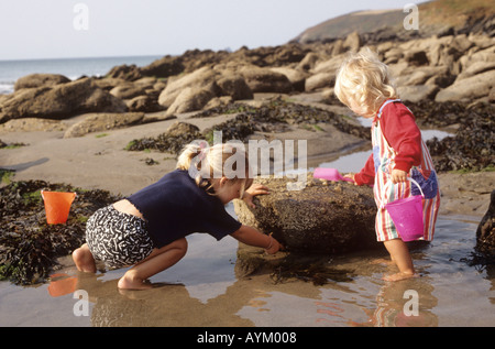 Young girls playing in a rock pool together on a beach in Cornwall in the United Kingdom - Stock Photo