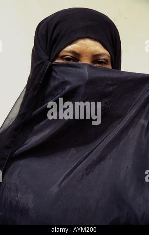 Young woman of Lamu wearing the traditional black buibui head covering Kenya coast East Africa - Stock Photo