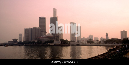 Singapore business district and Marina Bay at dusk - Stock Photo