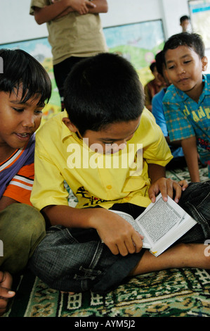 A young muslim boy in Banda Aceh Indonesia reads the Koran. - Stock Photo