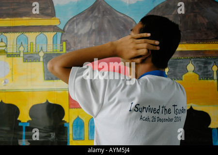 A young muslim boy in Banda Aceh Indonesia starts the midday prayer. - Stock Photo