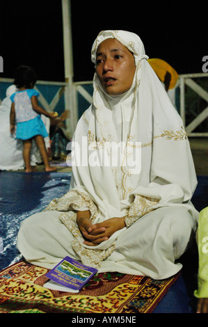 A young muslim girl in Banda Aceh Indonesia is praying on the night before the 1 year commemoration of the 2004 - Stock Photo
