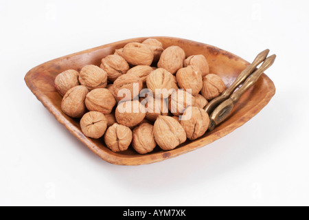 Whole walnuts in wooden bowl with brass nutcrackers - Stock Photo