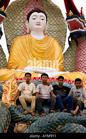 Stock photograph of young men seated on a statue beside the Aung Setkya Paya in Myanmar 2006 - Stock Photo