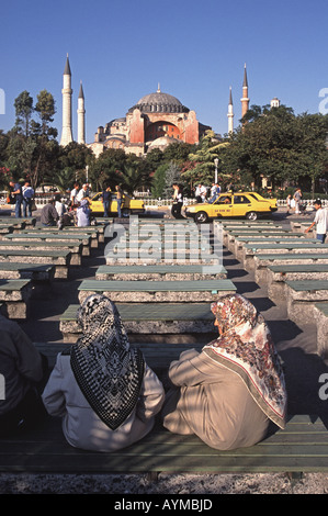 ISTANBUL, TURKEY. Traditionally-dressed Turkish women sitting opposite Aya Sofia in the Sultanahmet district. 2005. - Stock Photo