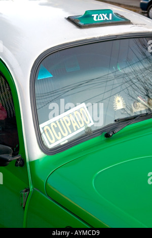 Empty Green VW Beetle Taxi parked by the curb in Mexico City with occupied sign in window - Stock Photo