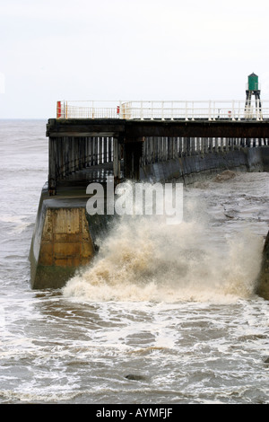 Waves crashing between breakwaters on Whitby pier Whitby North Yorkshire - Stock Photo