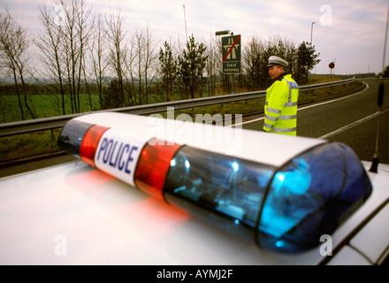 UK England M6 motorway transport policeman directing motorway traffic on slip road - Stock Photo