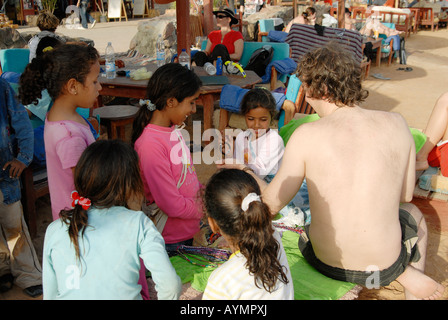 Bedouin children are selling bracelets to a white tourist in Dahab, Egypt - Stock Photo