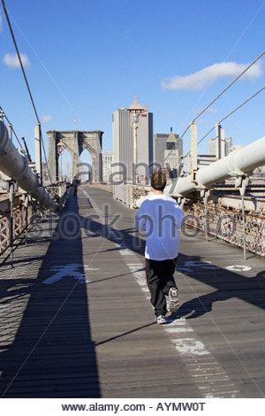 female running on Brooklyn bridge, New York, USA - Stock Photo