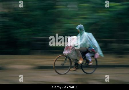 Cycling mom with two 2 children in heavy monsoon rain. Hue City Vietnam. Vietnam Viet Nam Asia traffic. - Stock Photo