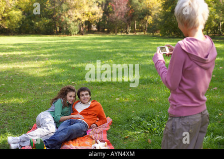 Blonde girl taking a picture of a teenage couple in a park - Stock Photo