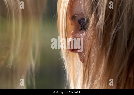young blonde haired teenage woman crying in front of dirty window with reflection illustrating student mental health - Stock Photo
