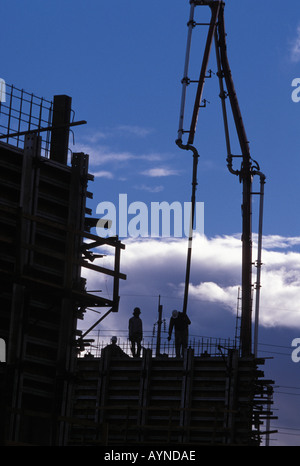 Construction workers on building site using concrete pumping equipment - Stock Photo