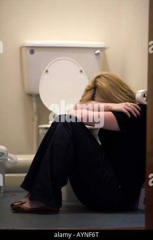 close up of arms and shoulders of blonde haired teenage woman sitting in fetal position on floor of toilet in the - Stock Photo