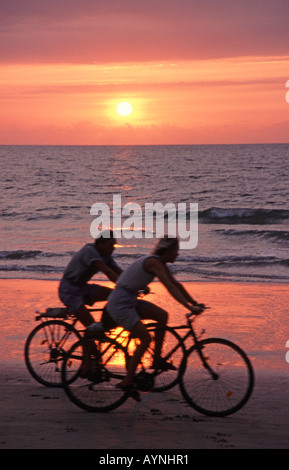 SOUTH GOA, INDIA. A cycling couple silhouetted against the setting sun on Colva Beach at Benaulim. January 2006. - Stock Photo