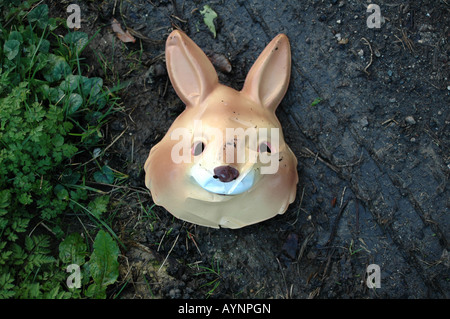 A rabbit mask on the side of a muddy track, slightly crushed but still smiling. - Stock Photo