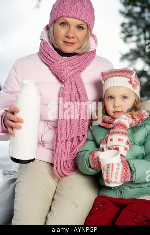 Mother and daughter in snow, woman holding a thermos flask - Stock Photo