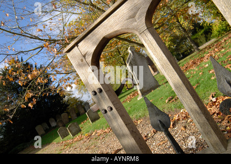 Peeping through a wooden arch at the gravestones beyond at Holy Trinity Parish Church  in Penn - Stock Photo