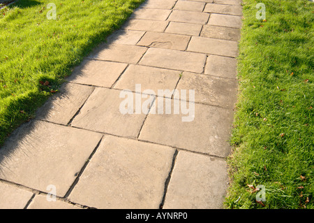 The path of old York slabs bordered by vivid green grass invites you to explore the churchyard - Stock Photo