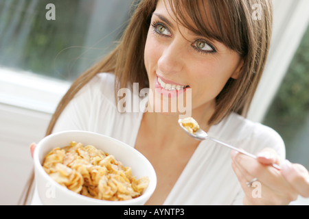 Brunette girl eating Cornflakes cereal - Stock Photo