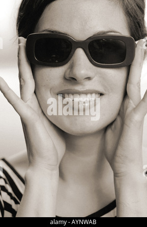 Junge dunkelhaarige Frau mit Sonnenbrille s w - Stock Photo