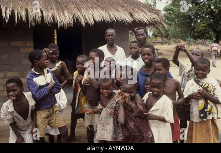 Children and village elders pose together for the camera in a typical village setting - Nkhotakota, Lake Malawi, - Stock Photo