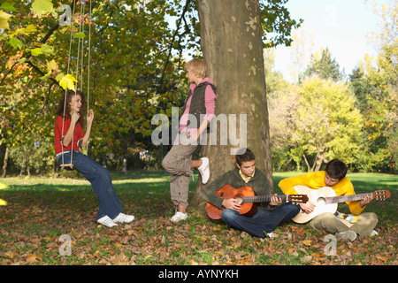 Four teenage people in a park - Stock Photo